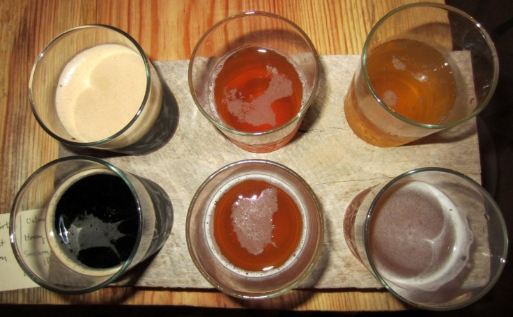 Sampler tray, clockwise from upper left: Corn Cob Smoked Porter, Thresher Coffee Saison, Cantilever Honey Melon Blonde, Spade Session IPA, Spoon Oatmeal Pale, and Cherry Stout.