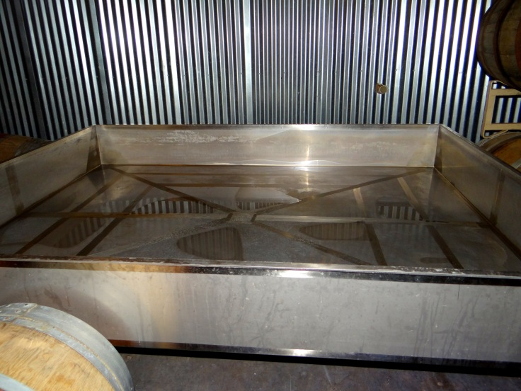 The coolship at de Garde where the wort is exposed to the ambient air while it cools. Notice the nearby wooden barrels that harbor yeast and bacteria that help to properly inoculate the wort.