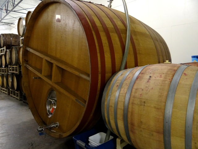 The large wooden vessel is called a foeder.  This one is full of fermenting beer as evidenced by the large hose coming out of the top.  The wine and spirit barrels visible in the background are used to age beer once the primary fermentation has finished.