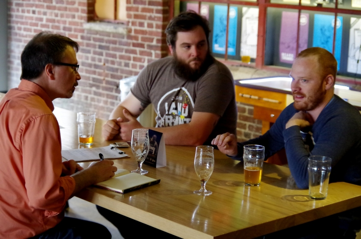 Co-owners Walt Keys (middle) and Adam Benner (right) recalling details of the twists and turns in the birth of Land Grant Brewing.