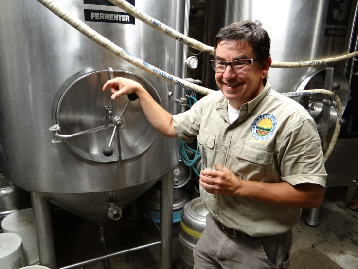 Angelo in front of one of the fermenters in the basement brewhouse of Barley's Brewing Co.